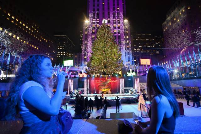 People drink as they stand near the tree after the 81st Annual Rockefeller Center Christmas Tree Lighting Ceremony in New York December 4, 2013.