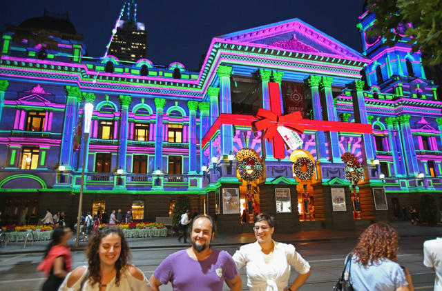 People look on as Melbourne Town Hall is illuminated with Christmas projections as Melbourne lights up for Christmas on December 13, 2012 in Melbourne, Australia.