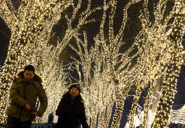 A Chinese couple walk past Christmas decorated trees on display in Beijing on December 10, 2012.