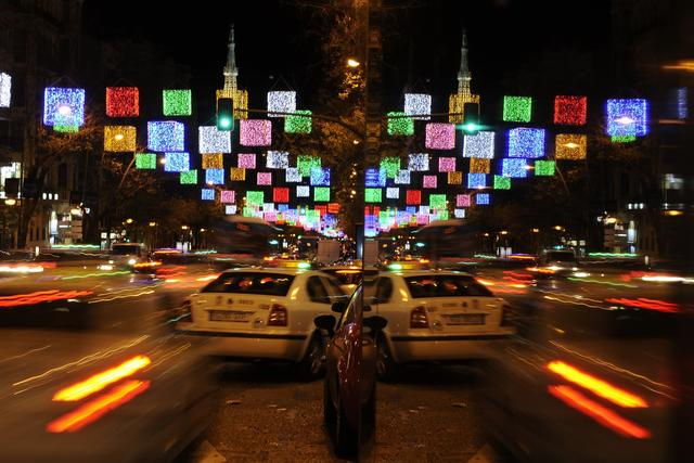 Cars passing under hanging Christmas lights are reflected on a glass in a street of Madrid, Spain on December 4, 2012. Streets of the capital are decked out in lights every year ahead of Christmas celebrations.