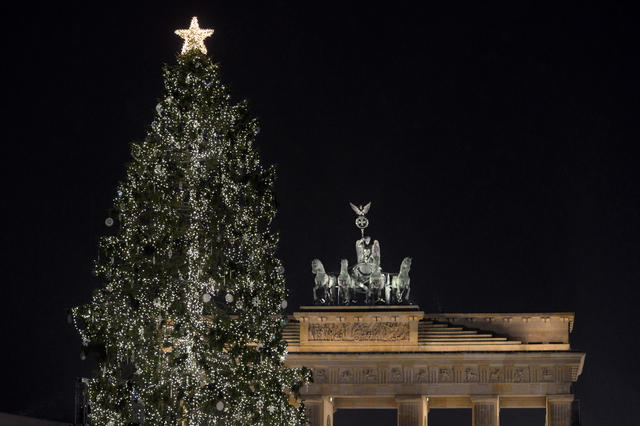 A christmas tree is illuminated in front of the Brandenburg Gate in Berlin, Germany, on December 2, 2012. The Christmas tree is a gift of the Norwegian embassy to Germany.