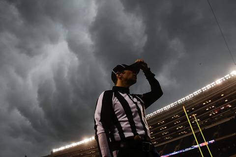 SCOTT STRAZZANTE: The story of today's Bears' win was the weather. Midway through the 1st quarter a powerful storm blew in causing a nearly two-hour delay. As the security guards tried to rush me off the field, I hung around long enough to get a photo of back judge Dino Paganelli holding on to his hat as he headed for cover. The low angle accentuated the stormy sky and created a nice weather feature.