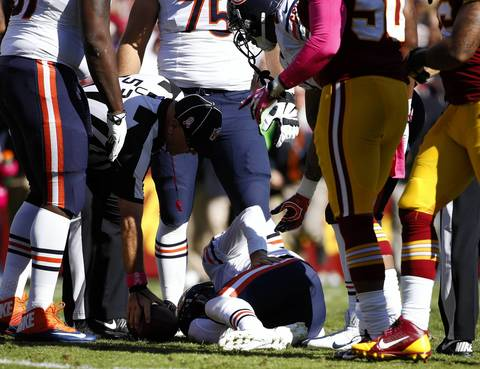 José M. Osorio : I like this photo of Chicago Bears quarterback Jay Cutler (6) laying on the ground, injured after a sack in the second quarter at FedEx Field. I photographed the play but noticed that hand of one of the linemen reaching out, it is a subtle gesture in a rough sport. Cutler left the game and didn't return.