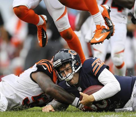 BRIAN CASSELLA: My favorite image of the game is of Jay Cutler sliding after a long scramble in the fourth quarter, kicking up a spray of grass and knocking his chinstrap into his face. I was on the Bears sideline and the look right into his face gives the picture some impact, plus the two Bengals jumping over him makes it a bit more unusual. Even though the play went for an 18-yard gain, visually it looks more like Cutler is being knocked around and having a tough day. When the Bears held on for the win, the value of the picture moved from a chance at the front page to a small image inside the sports section.