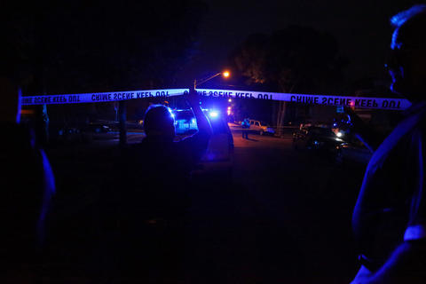Chicago police cross under the police tape as they investigated the scene where a man was shot and killed by police after he raised a 9-millimeter handgun in their direction after bailing from a moving car in the 1600 block of South Springfield Avenue in Chicago.