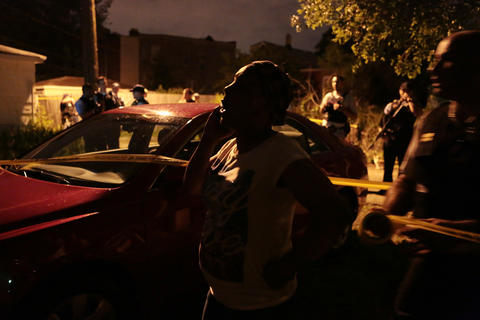 The mother of a man who was shot and killed by police after he raised a 9-millimeter handgun in their direction after bailing from a moving car talks on her phone at the scene in the 1600 block of South Springfield Avenue in Chicago.