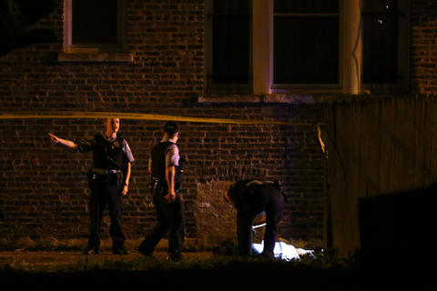 Chicago police investigate the scene where a man was shot and killed by police after he raised a 9-millimeter handgun in their direction after bailing from a moving car in the 1600 block of South Springfield Avenue in Chicago.