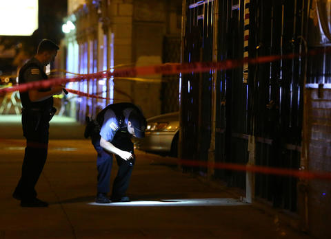 Chicago police investigate the scene where four people were shot, including one who died, inside a club on 79th Street between Ellis and Ingleside avenues in Chicago.