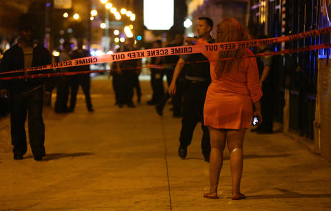 A woman motions that she needs to retrieve her car which was parked in a crime scene Chicago police investigate where four people were shot, including one who died, inside a club on 79th Street between Ellis and Ingleside Avenues in Chicago.