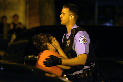A woman who identified herself as the mother of a man who was killed is held back by police as she is overcome with emotion after arriving at the scene where people three were shot, including the one who died, in the 2500 block of South Ridgeway Avenue in Chicago.