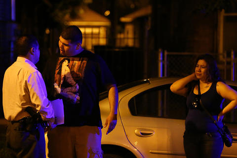 A man confronts a Chicago detective during questioning at the scene where three people were shot, including one who died, in the 2500 block of South Ridgeway Avenue in Chicago.