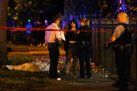 Chicago police investigate the scene where three people were shot, including one who died, in the 2500 block of South Ridgeway Avenue in Chicago.