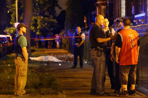 Chicago police talk with a man who identified himself as the cousin of a man who was killed at the scene where three people were shot, including the one who died, in the 2500 block of South Ridgeway Avenue in Chicago.