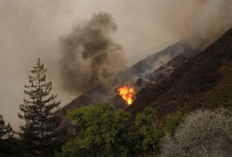 A blaze flares up during a wild fire in Big Sur, California, December 17, 2013.  A wildfire that erupted in a scenic stretch of California's central coastline late Sunday night has destroyed at least 15 homes and forced many residents to evacuate, county and fire officials said.