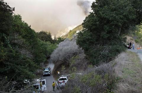 Police and fire vehicles sit at the entrance to a canyon during a wild fire in Big Sur, California, December 17, 2013. A wildfire that erupted in a scenic stretch of California's central coastline late Sunday night has destroyed at least 15 homes and forced many residents to evacuate, county and fire officials said.