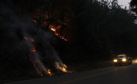 A wildfire burns down to Highway 1 in Big Sur, California, December 17, 2013. Crews battling a wildfire along central California's scenic Big Sur coastline were on guard against a possible shift in winds on Tuesday, after the blaze destroyed at least 15 dwellings and forced 100 people to flee their homes, fire and county officials said.