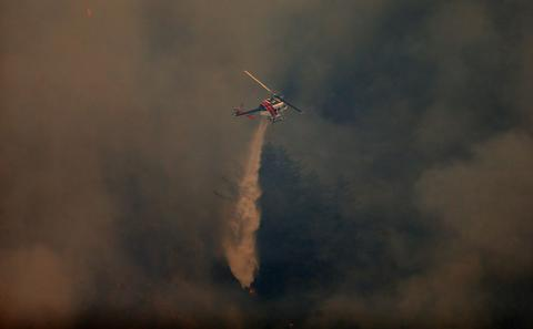 A Cal Fire helicopter drops water onto a wildfire near Pfeiffer Ridge in Big Sur, Calif., on Tuesday, Dec. 17, 2013. The fire has burned about 550 acres in the Los Padres National Forest. (Aric Crabb/Bay Area News Group/MCT)