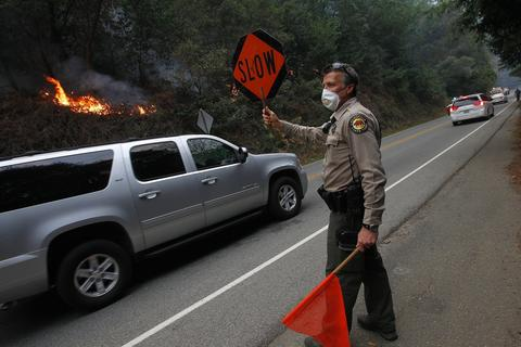 State Park Ranger Phil Bergman directs traffic along Highway 1 near the Pfeiffer Ridge fire in Big Sur, Calif., on Tuesday, Dec. 17, 2013. The fire has burned about 550 acres in the Los Padres National Forest. (Aric Crabb/Bay Area News Group/MCT)