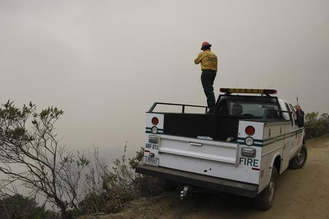 Firefighter Oscar Vargas spots for helicopter drops on Pfeiffer Ridge in Big Sur, California, December 17, 2013. The wildfire that erupted in a scenic stretch of California's central coastline late Sunday night has destroyed at least 15 homes and forced many residents to evacuate, county and fire officials said.