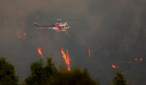 A Cal Fire helicopter flies over flames near Pfeiffer Ridge in Big Sur, Calif., on Tuesday, Dec. 17, 2013. The fire has burned about 550 acres in the Los Padres National Forest. (Aric Crabb/Bay Area News Group/MCT)