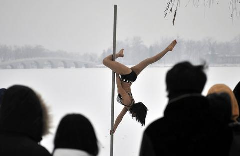 This picture taken on December 17, 2013 shows people watching a pole dancer practise after it snowed in Tianjin during a promotional event by members of China's national pole dancing team and students of the sport.