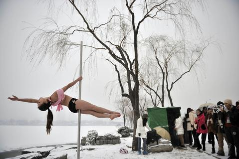 This picture taken on December 17, 2013 shows people watching a pole dancer (L) practise after it snowed in Tianjin during a promotional event by members of China's national pole dancing team and students of the sport.