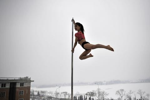This picture taken on December 17, 2013 shows a pole dancer practising after it snowed in Tianjin during a promotional event by members of China's national pole dancing team and students of the sport.