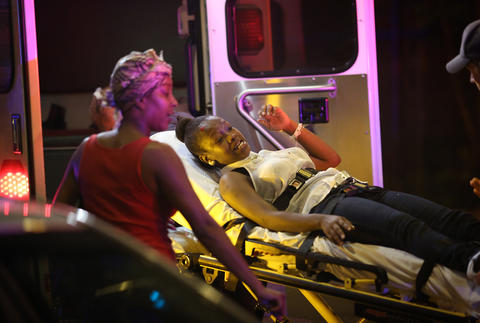 Emergency personnel transport victims from the scene where at least 13 people, including a 3-year-old, were shot at Cornell Square Park in the Back of the Yards neighborhood of Chicago.