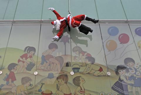 A member of the special police force dressed in a Santa suit descends from the roof of a paediatric clinic in Ljubljana, as part of a Christmas performance for patients of the clinic, December 18, 2013.