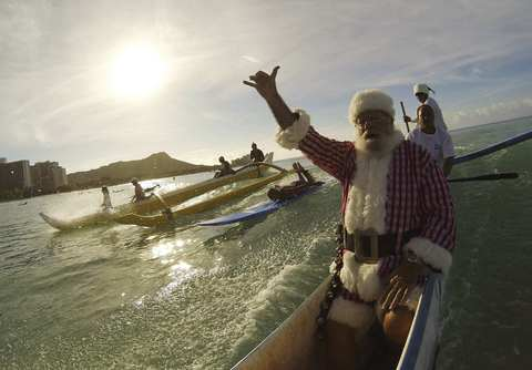 Donald Boyce, who dressed up as Santa Claus, catches a wave in an outrigger canoe off Waikiki Beach in Honolulu, Hawaii, December 14, 2013.