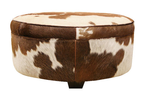 "The preferred animals appear to be elephants and dogs, which will be popular for wallpaper, furniture, and bedding. Animals have even crept over to kids decor. ""They are also bringing it out in different colors - zebra print in hot pink and blue,"" she says. Cowboy Hide Round Ottoman from Arhaus"