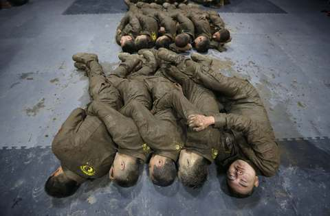 Students hold each other for warmth as they sleep during a break in between high intensity training at Tianjiao Special Guard/Security Consultant camp on the outskirts of Beijing December 1, 2013. Former Chinese soldier Chen Yongqing has big ambitions for his bodyguard training school Tianjiao, which he says is China's first professional academy to train former soldiers and others as personal security guards. Chen charges 500,000 yuan ($82,400) a year for each protector as China's rich and famous look to bolster their safety and sense of importance.
