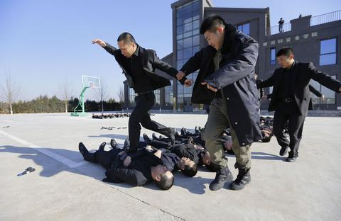 Students run over the bodies of fellow trainees at the Tianjiao Special Guard/Security Consultant training camp on the outskirts of Beijing December 11, 2013. Former Chinese soldier Chen Yongqing has big ambitions for his bodyguard training school Tianjiao, which he says is China's first professional academy to train former soldiers and others as personal security guards. Chen charges 500,000 yuan ($82,400) a year for each protector as China's rich and famous look to bolster their safety and sense of importance.