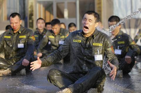 A trainee reacts as he is drenched with water during Tianjiao Special Guard/Security Consultant training on the outskirts of Beijing December 1, 2013. Former Chinese soldier Chen Yongqing has big ambitions for his bodyguard training school Tianjiao, which he says is China's first professional academy to train former soldiers and others as personal security guards. Chen charges 500,000 yuan ($82,400) a year for each protector as China's rich and famous look to bolster their safety and sense of importance.