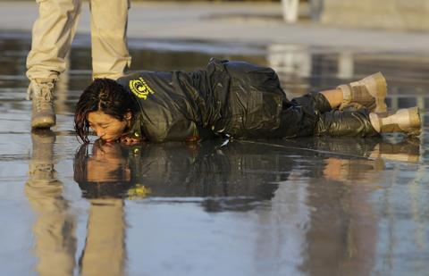 A female trainee lies on the ground after being drenched with water during Tianjiao Special Guard/Security Consultant training on the outskirts of Beijing December 1, 2013. Former Chinese soldier Chen Yongqing has big ambitions for his bodyguard training school Tianjiao, which he says is China's first professional academy to train former soldiers and others as personal security guards. Chen charges 500,000 yuan ($82,400) a year for each protector as China's rich and famous look to bolster their safety and sense of importance.