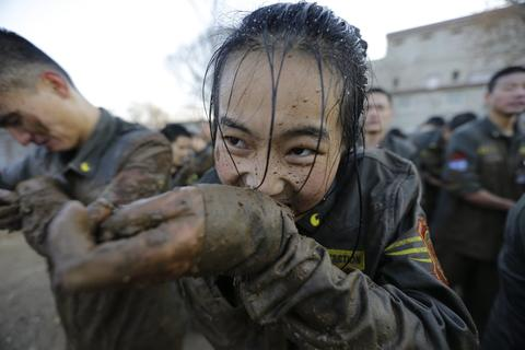 A female student opens her cufflinks with her teeth, after crawling through mud at Tianjiao Special Guard/Security Consultant camp on the outskirts of Beijing December 12, 2013. Former Chinese soldier Chen Yongqing has big ambitions for his bodyguard training school Tianjiao, which he says is China's first professional academy to train former soldiers and others as personal security guards. Chen charges 500,000 yuan ($82,400) a year for each protector as China's rich and famous look to bolster their safety and sense of importance.