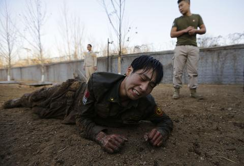 A student reacts as he crawls on the ground during Tianjiao Special Guard/Security Consultant training on the outskirts of Beijing December 1, 2013. Former Chinese soldier Chen Yongqing has big ambitions for his bodyguard training school Tianjiao, which he says is China's first professional academy to train former soldiers and others as personal security guards. Chen charges 500,000 yuan ($82,400) a year for each protector as China's rich and famous look to bolster their safety and sense of importance.