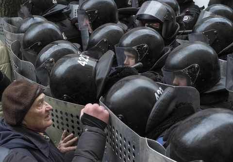 A woman stands in front of Interior Ministry personnel as they block pro-EU demonstrators near the Ukrainian Ministry of Internal Affairs in Kiev December 20, 2013.