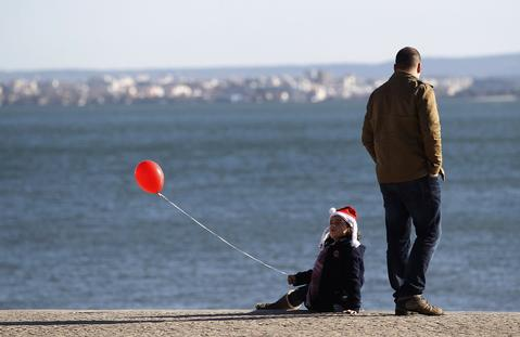 A girl wearing a Santa's hat plays with a red ballon near Tagus River in Lisbon December 20, 2013.