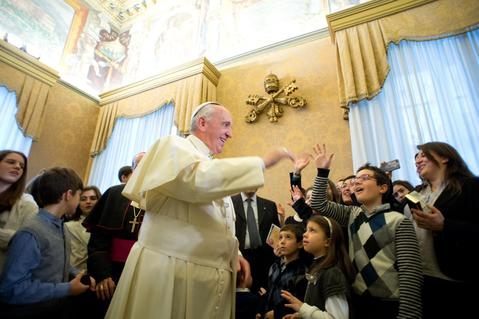 Pope Francis waves during an audience with a delegation of youths of the Italian Catholic Action Association at the Vatican, on December 20, 2013.