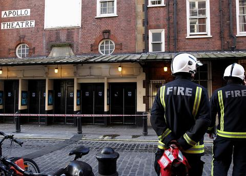 Fireman stand outside the Apollo Theatre following the partial collapse of the theatre's roof last night, on December 20, 2013 in London, England.