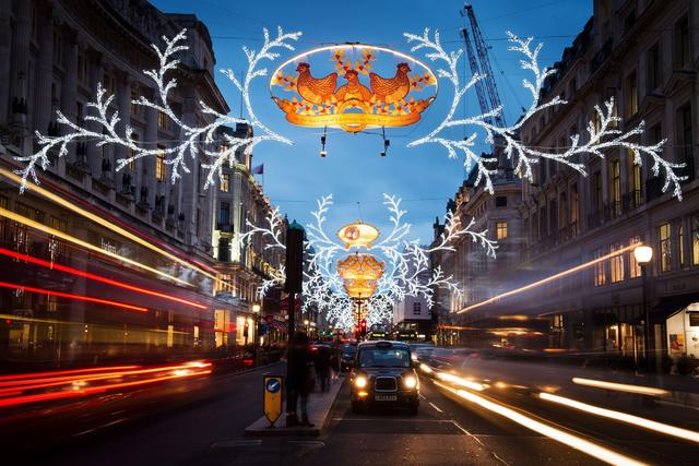 Traffic and pedestrians move beneath Christmas lights displayed on Regent Street in central London on December 18, 2013.