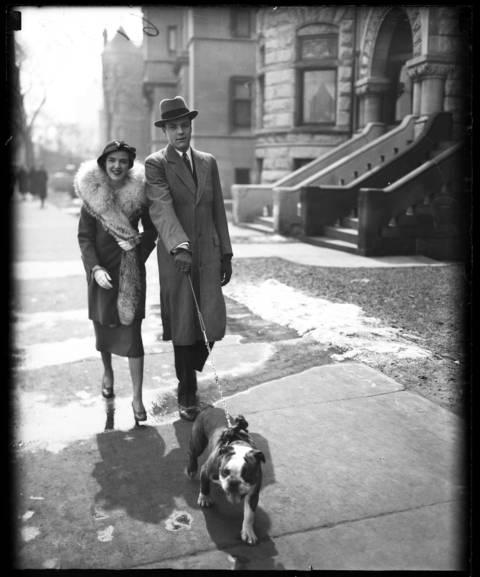 """Mr. and Mrs. John Barnes, part of Chicago's """"society"""", stroll down Lake Shore Drive on Easter Sunday with their dog """"Dandy"""", circa April 5, 1932."""