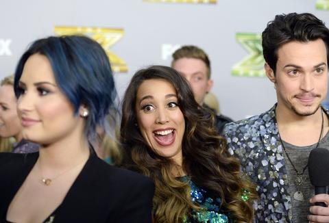 "Sierra Deaton (C) photobombs judge Demi Lovato's interview as Alex Kinsey (L) speaks to a television reporter backstage after the folk duo won ""The X Factor"" in Los Angeles, California, December 19, 2013. Winners Kinsey and Deaton won a $1 million recording contract with Sony Music Entertainment."