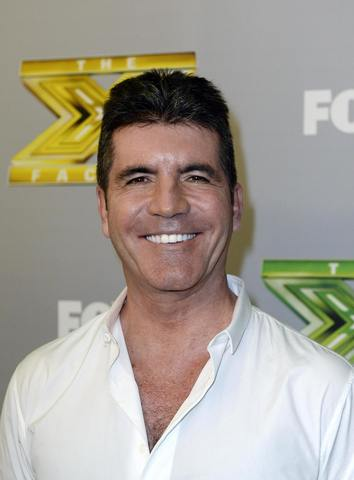 "Judge Simon Cowell poses backstage after ""The X Factor"" finale in Los Angeles, California, December 19, 2013. Winners Alex Kinsey and Sierra Deaton won a $1 million recording contract with Sony Music Entertainment."