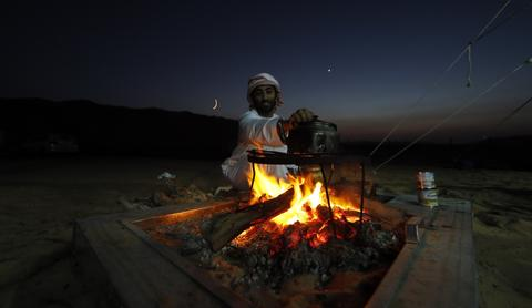 An Emirati heats a tea pot over an open fire at the Liwa desert, 220 kms west of Abu Dhabi, on the sidelines of the Mazayin Dhafra Camel Festival on December 21, 2013. The festival, which attracts participants from around the Gulf region, includes a camel beauty contest, a display of UAE handcrafts and other activities aimed at promoting the country's folklore.