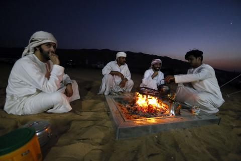 Emirati gather around an open fire at the Liwa desert, 220 kms west of Abu Dhabi, on the sidelines of the Mazayin Dhafra Camel Festival on December 21, 2013. The festival, which attracts participants from around the Gulf region, includes a camel beauty contest, a display of UAE handcrafts and other activities aimed at promoting the country's folklore.