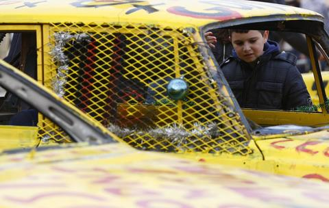 A boy looks into a car before a demolition derby organised by the Malta Motor Sports Association to raise funds for charity in Ta' Qali, outside Valletta, December 22, 2013. The drivers have one ultimate aim - that their vehicle, or what's left of it, remains the only one standing.