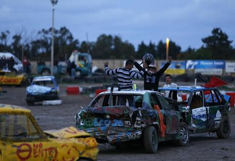 The joint winners celebrate after a demolition derby, organized by the Malta Motor Sports Association to raise funds for charity, ended in a tie in Ta' Qali, outside Valletta, December 22, 2013. The drivers have one ultimate aim - that their vehicle, or what's left of it, remains the only one standing.