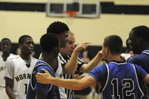 East Hartford High School's, Trayson Patterson, 2, left, smiles as the referee appears to call a technical foul on East Catholic High School forward, John Lambert, 55, as he laughs at Patterson, for getting a technical foul called on him a few seconds earlier in the fourth period. Patterson had stood by the team huddle of East Catholic, and received a technical after a series of shoving incidents.